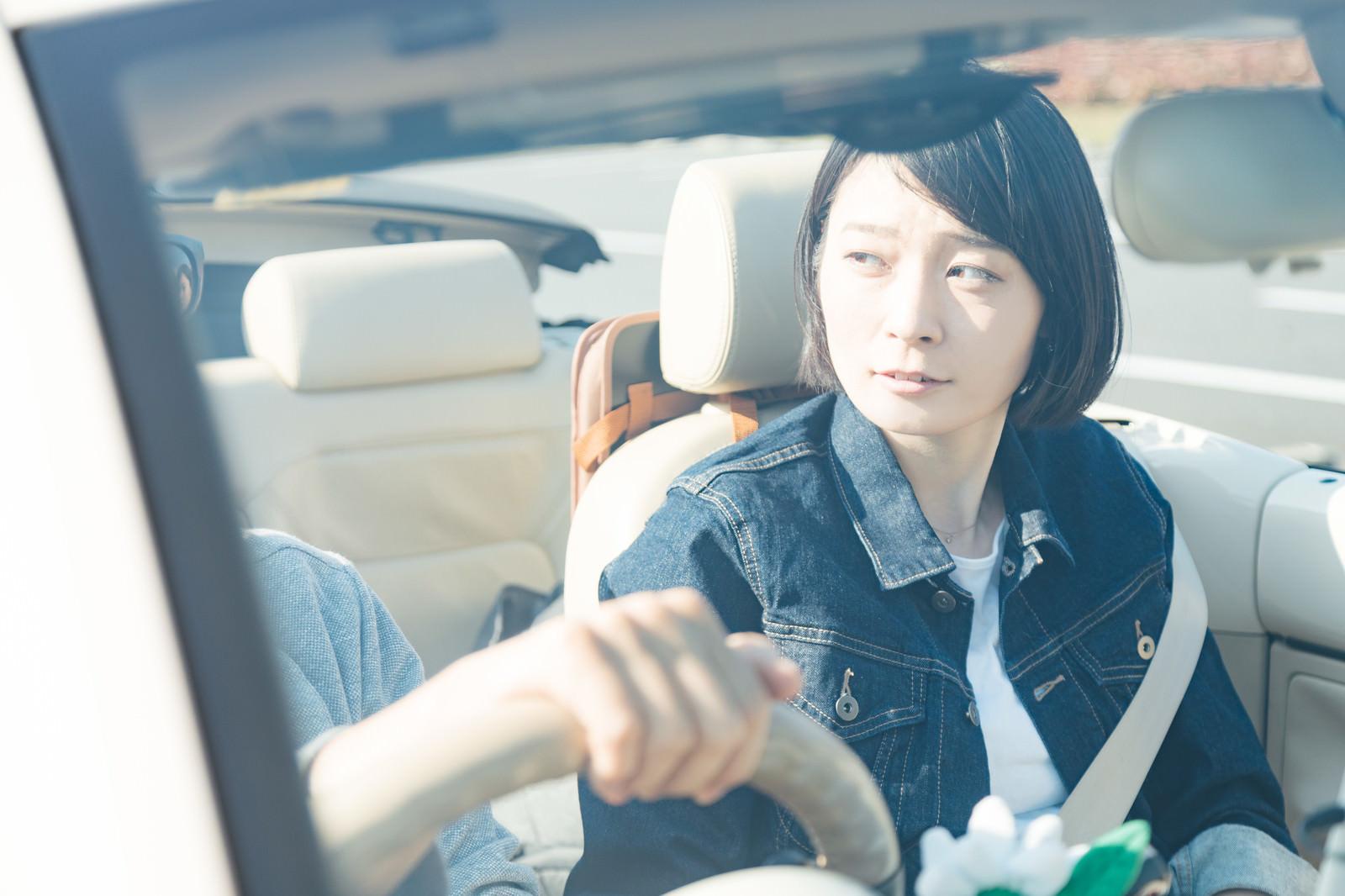 「オープンカーを運転する彼がイキってて少し心配そうな彼女」の写真[モデル:たけべともこ]