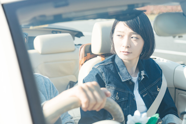 オープンカーを運転する彼がイキってて少し心配そうな彼女の写真