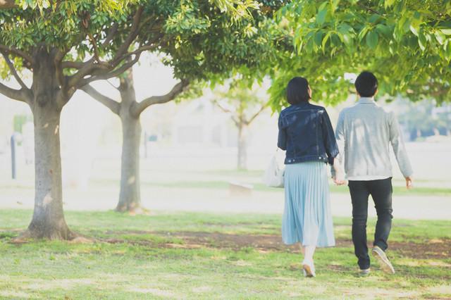新緑の公園を歩く男女カップルの写真