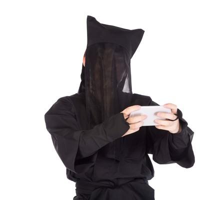 「スマホゲームに夢中な黒子さん」の写真素材