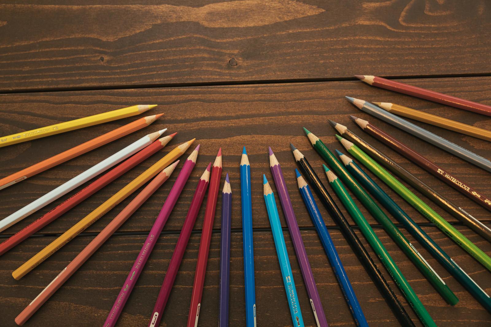 「木目のテーブルとカラフル色鉛筆」の写真