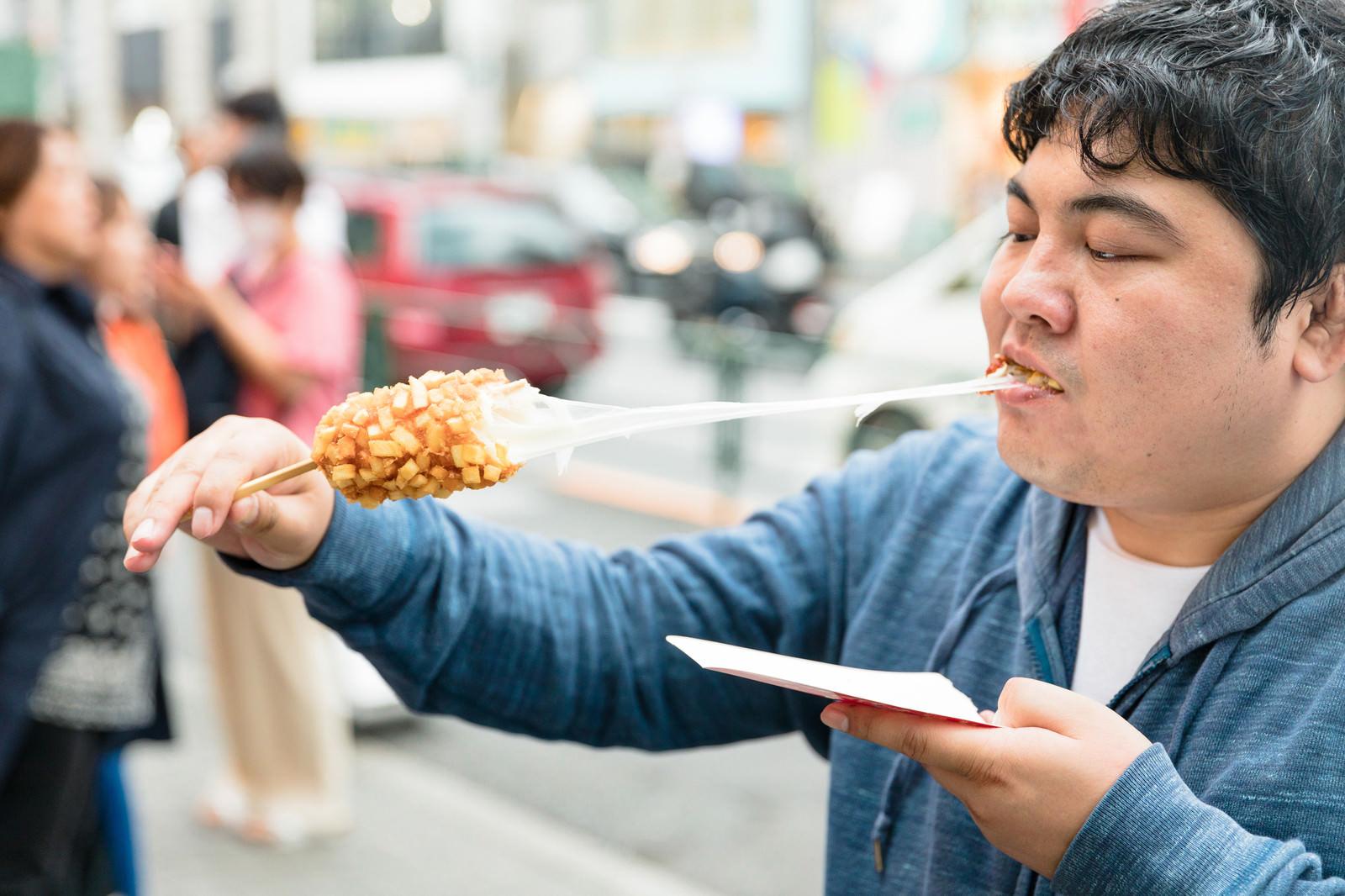 「伸びるチーズを楽しむチーズドッグ」の写真[モデル:段田隼人]