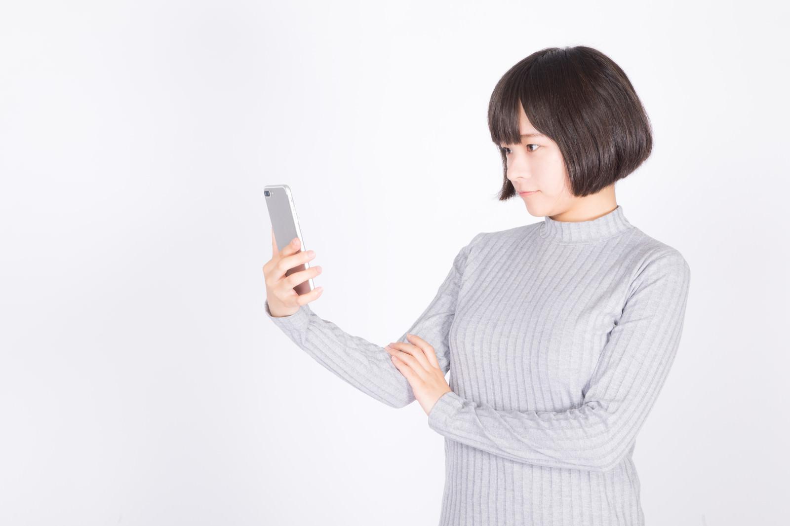 「スマホを確認する女性」の写真[モデル:千歳]