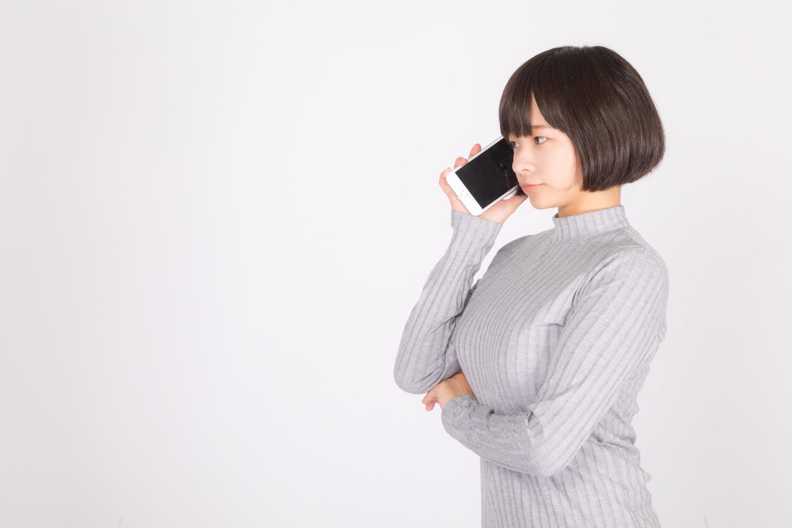 「スマートフォンで音声通話する若い女性」の写真[モデル:千歳]