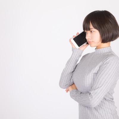「スマートフォンで音声通話する若い女性」の写真素材