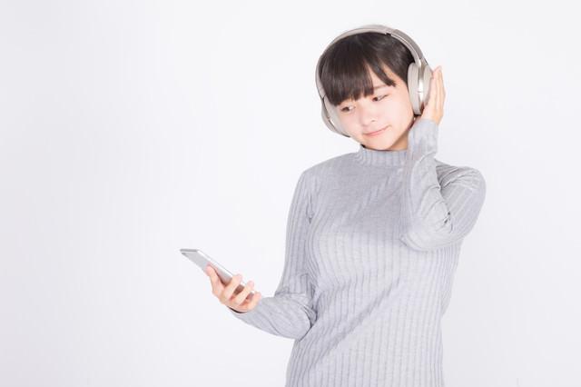 ワイヤレスヘッドホンで音楽を楽しむ若い女性の写真