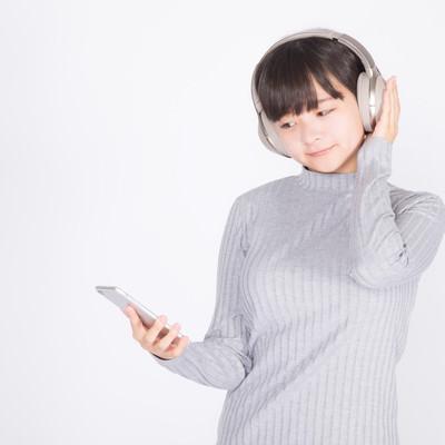 「ワイヤレスヘッドホンで音楽を楽しむ若い女性」の写真素材
