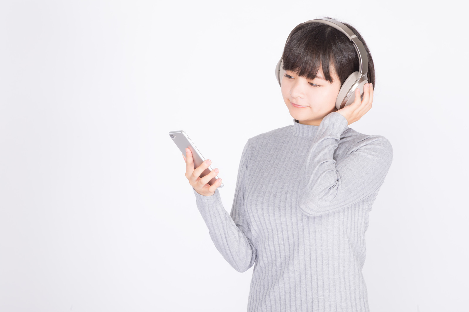 「スマホで音楽を楽しむ女性」の写真[モデル:千歳]