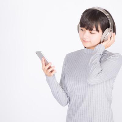 「スマホで音楽を楽しむ女性」の写真素材