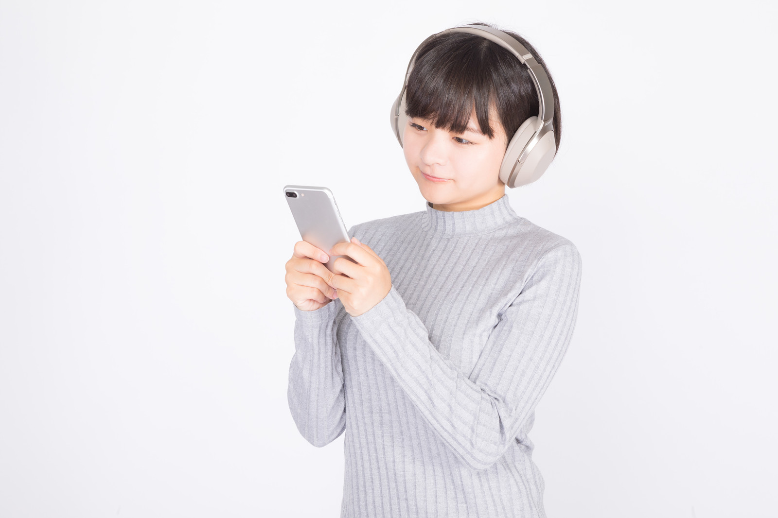 「スマホで音楽を聴く女性」の写真[モデル:千歳]