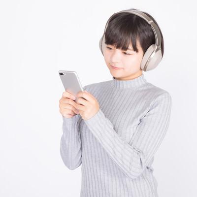 「スマホで音楽を聴く女性」の写真素材