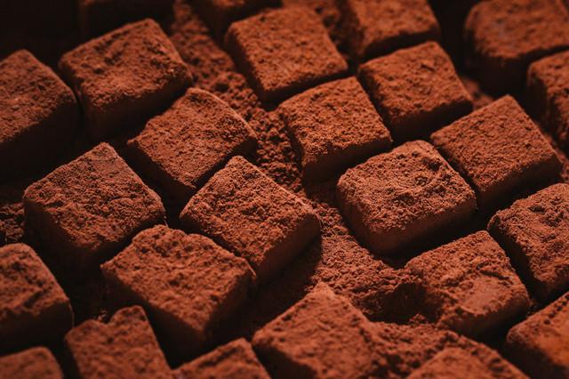 ココアパウダーに埋まる四角い生チョコの写真