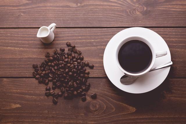 散らばるコーヒー豆と淹れたてのコーヒーの写真