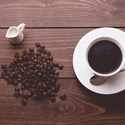 「散らばるコーヒー豆と淹れたてのコーヒー」の写真素材