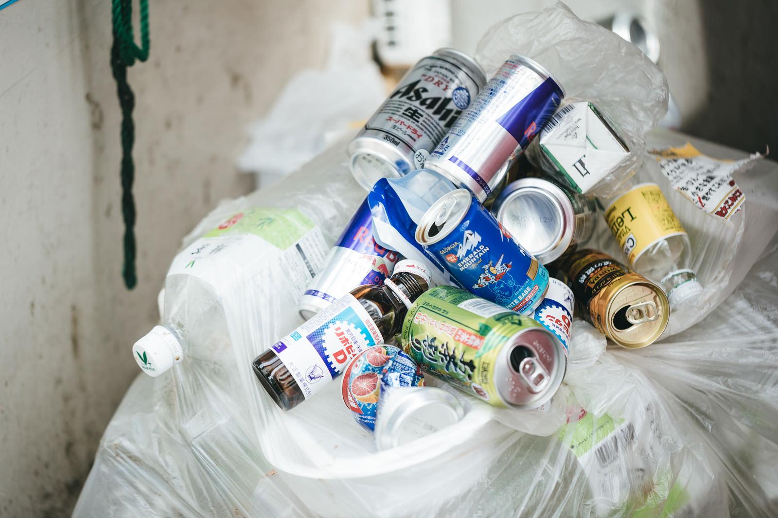 「ゴミ袋がある場所に捨てられていく空き缶の山」の写真