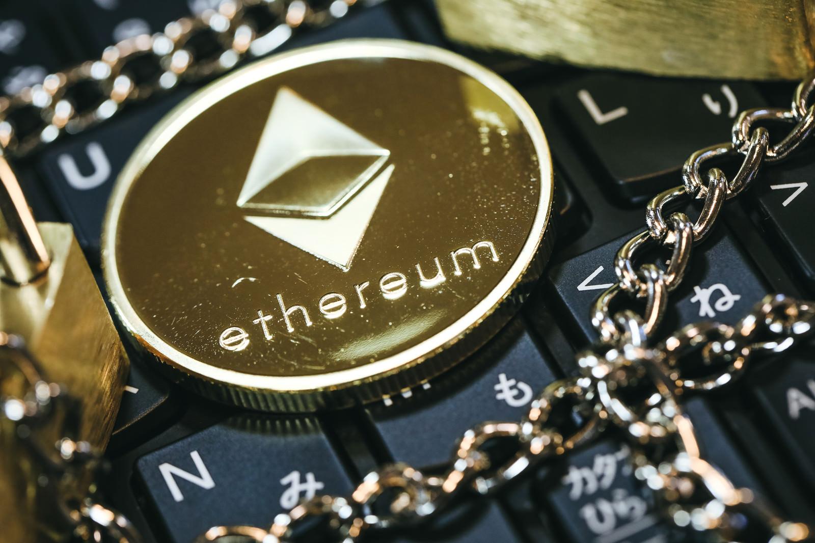「キーボード上に置いたチェーンとアルトコイン(ETH)」の写真