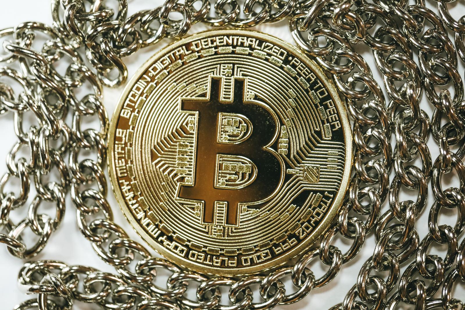 「チェーンの中心にあるビットコイン(仮想通貨)」の写真
