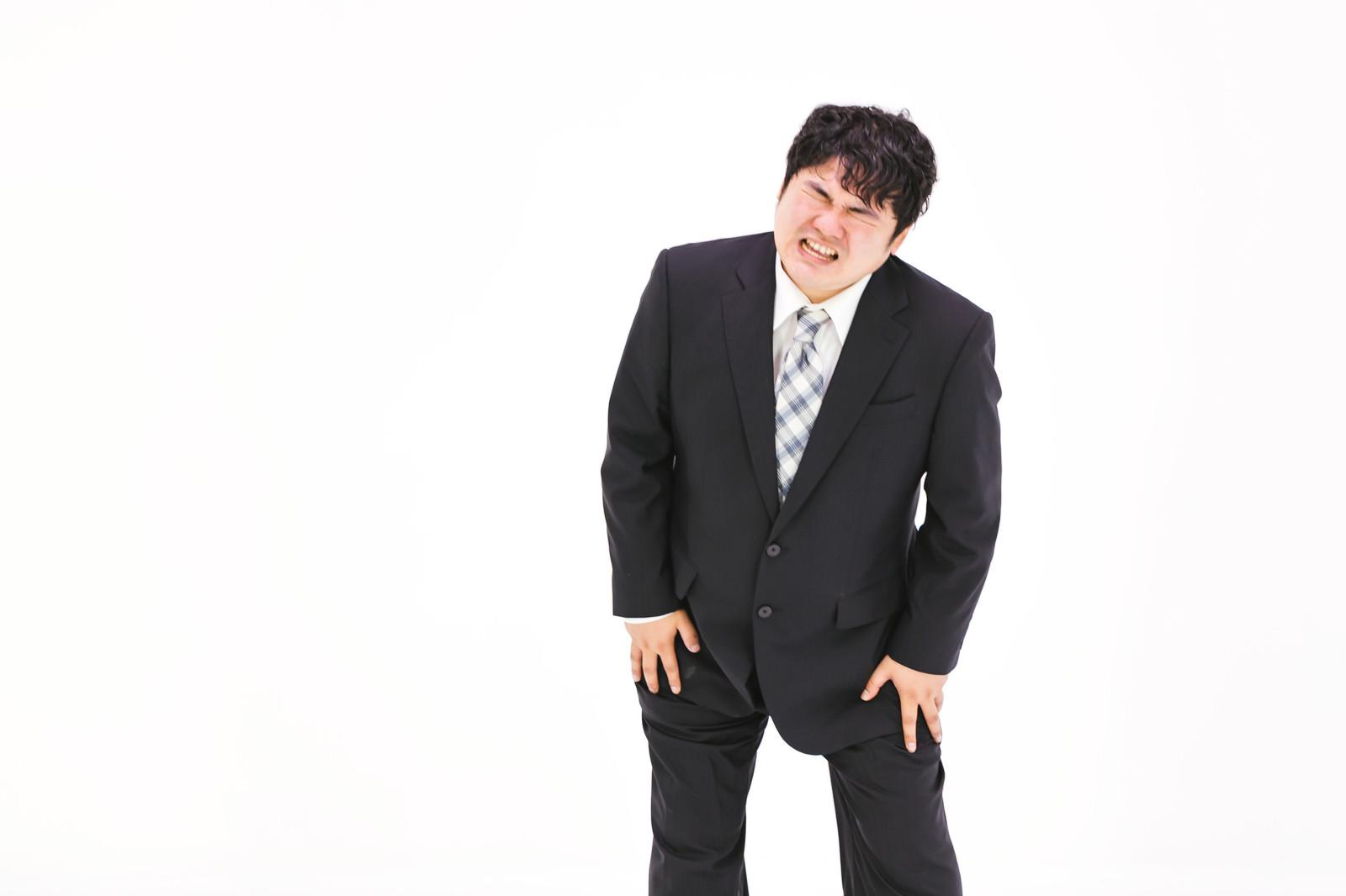 「膝を痛めてしまった肥満男性」の写真[モデル:段田隼人]