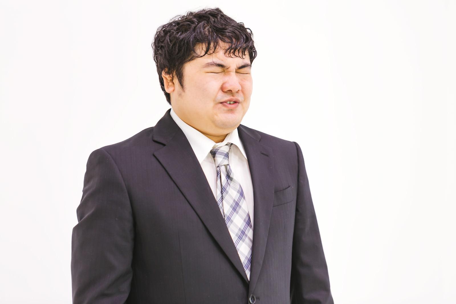 「苦渋の色を浮かべる会社員」[モデル:段田隼人]