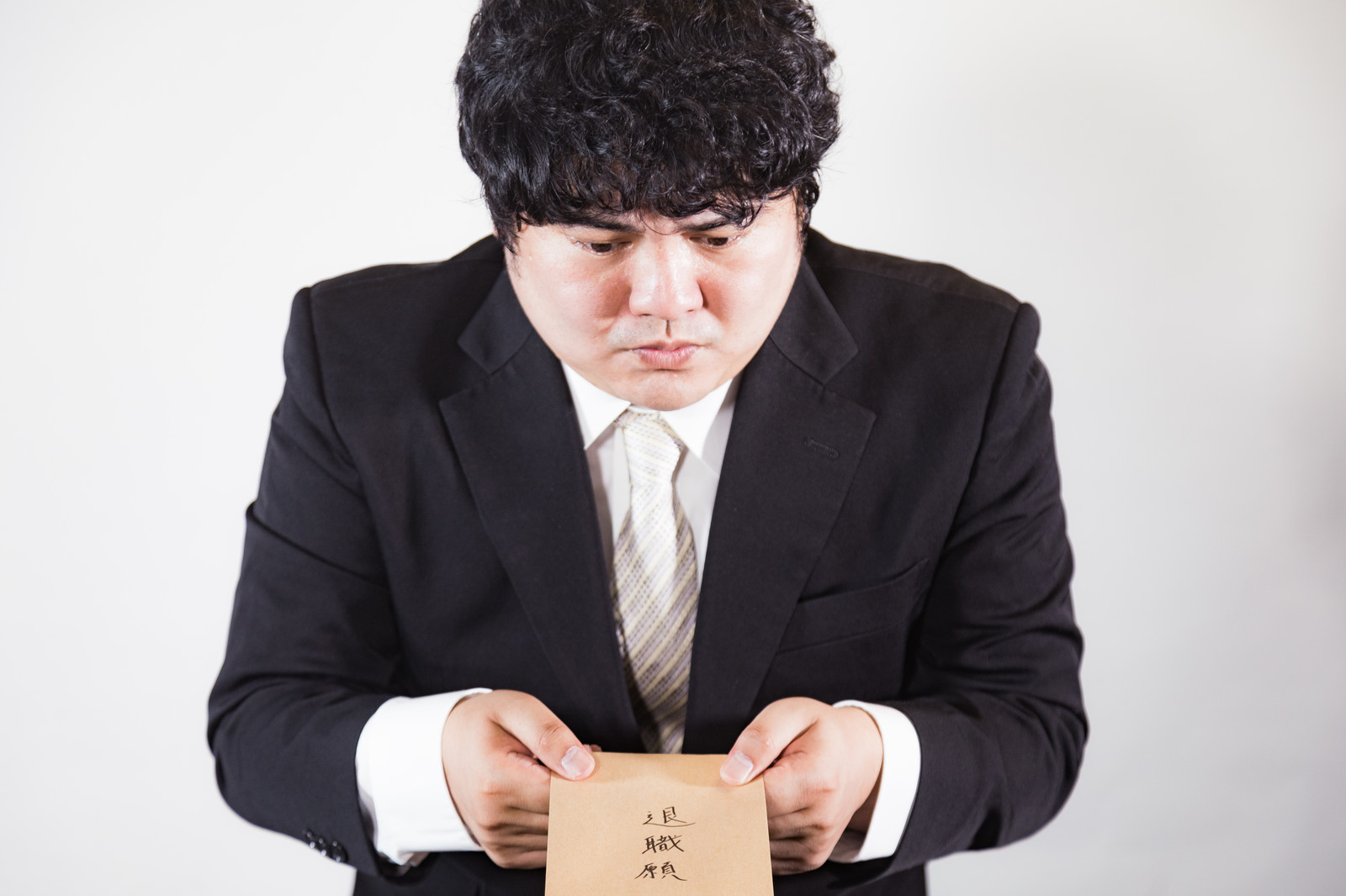 「退職願を渡す社員」の写真[モデル:段田隼人]