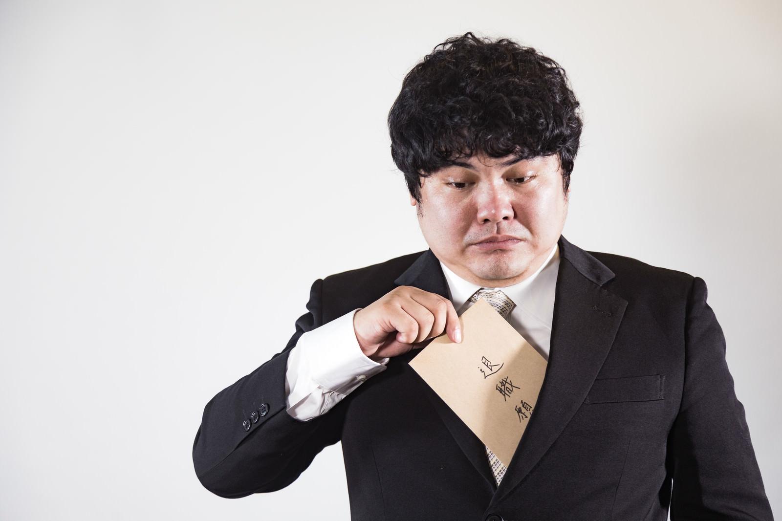 「退職願いが受理されないかと不安な会社員」の写真[モデル:段田隼人]