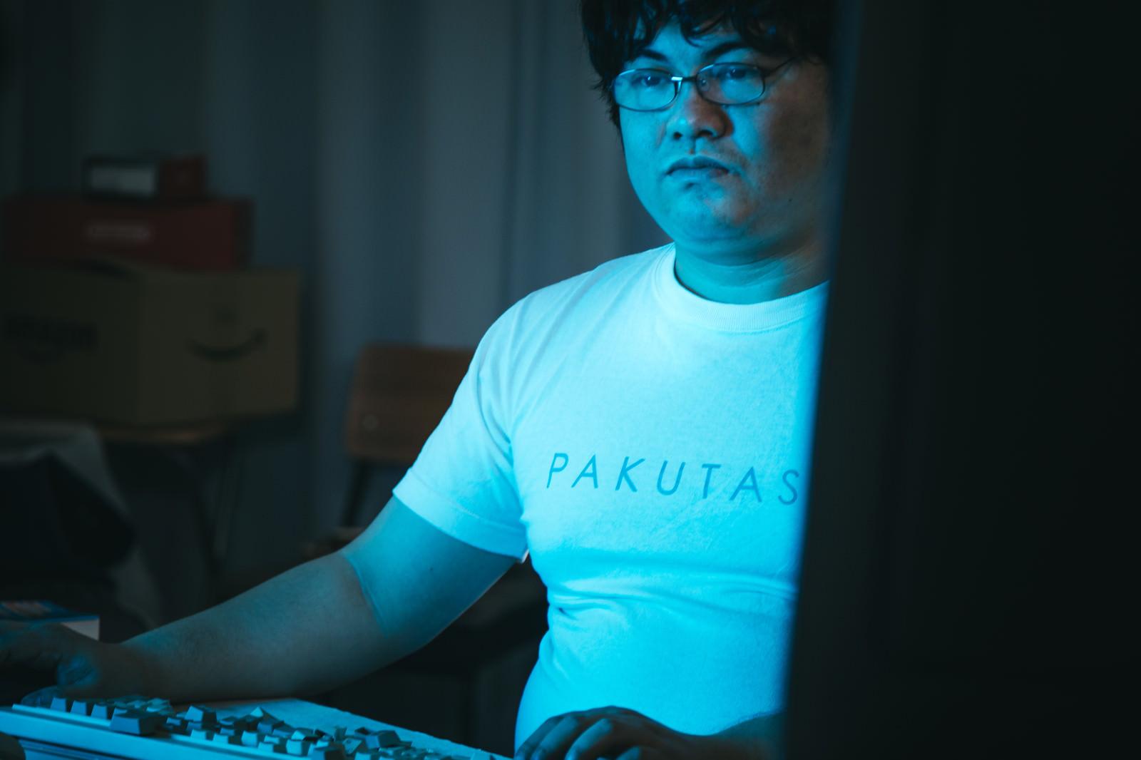 「モニターの明かりで淡々と作業をするエンジニア」の写真[モデル:段田隼人]