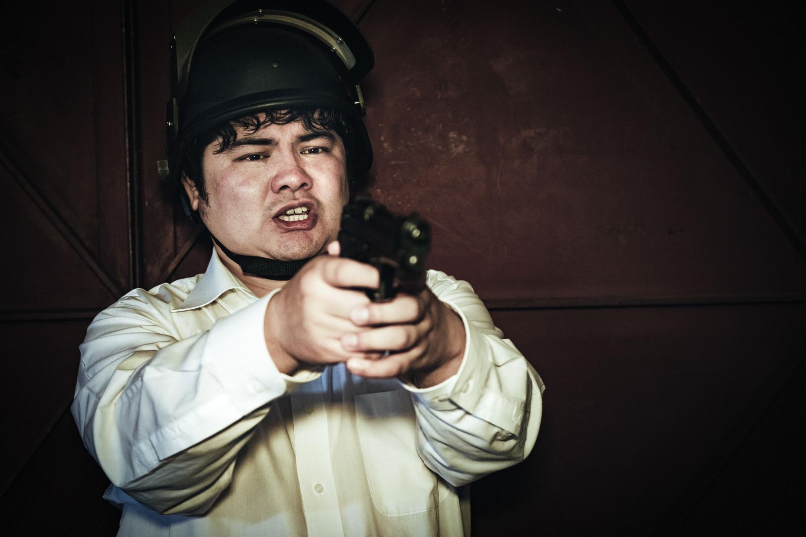 「対峙した瞬間、慌てて拳銃を構えてしまう荒野初心者」の写真[モデル:段田隼人]