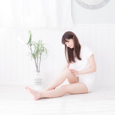 脚の脱毛後に保湿をする女性の写真