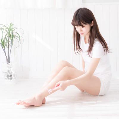 脚の産毛を剃る女性の写真