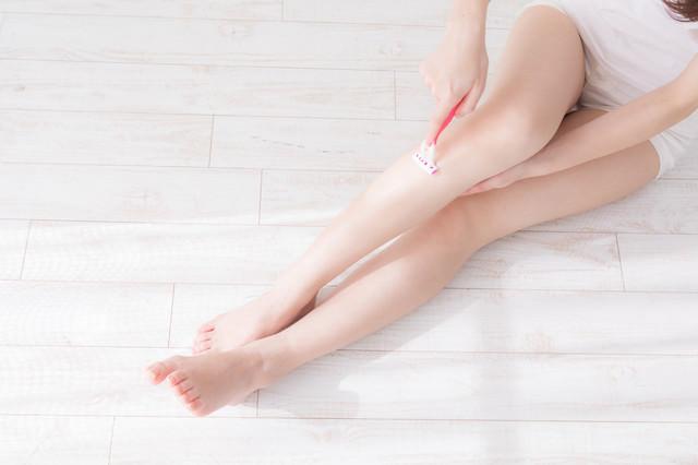 脛あたりのムダ毛を処理する女性の写真