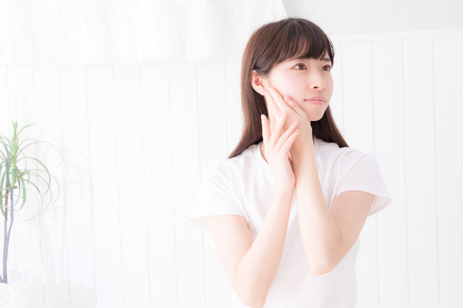 「顔に手を添え遠くを見つめる女性」の写真[モデル:川子芹菜]