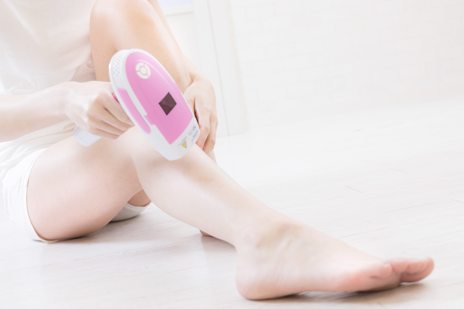 「セルフ脱毛器で足の脱毛を行う女性」の写真[モデル:緋真煉]