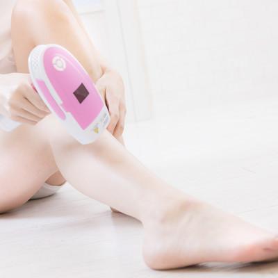 セルフ脱毛器で足の脱毛を行う女性の写真