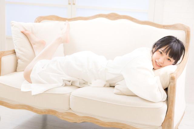 バスローブ姿でソファーに寝転ぶ若い女性の写真