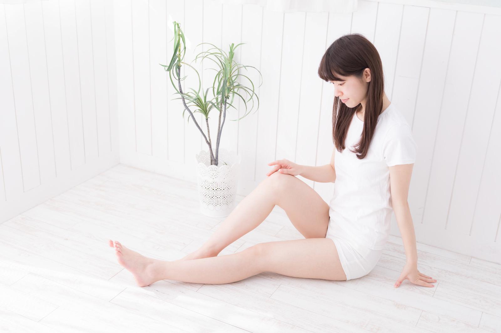 「立てた右膝に手を添えて座る女性」の写真[モデル:川子芹菜]