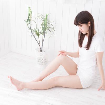 立てた右膝に手を添えて座る女性の写真
