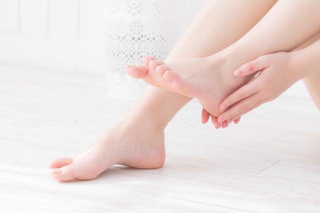 左足のかかとを両手でケアする女性の写真