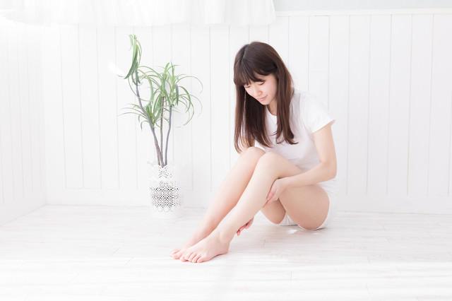 両足を立てて座りふくらはぎをマッサージする女性の写真