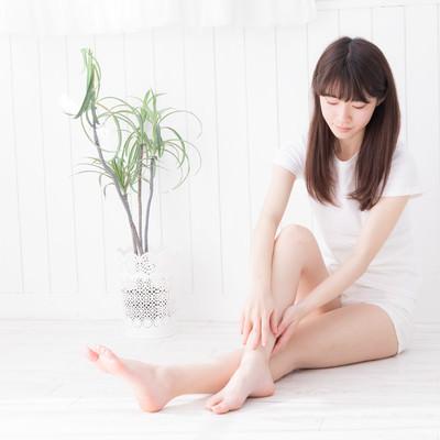 右足のふくらはぎを両手でマッサージする女性の写真