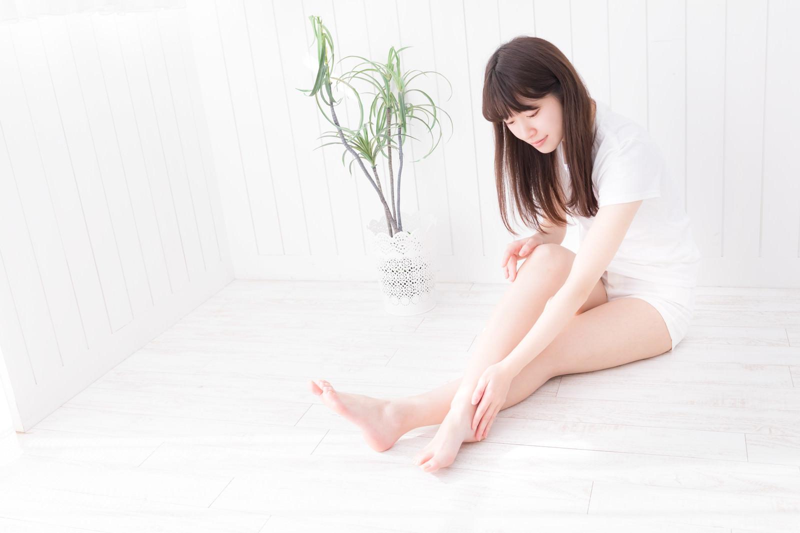 「伸ばした右足の膝下を覗き込む女性」の写真[モデル:川子芹菜]