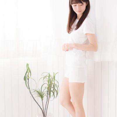 白いカーテンの前に立つ女性の写真