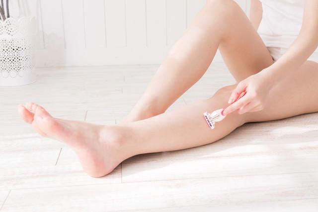 T字カミソリで膝下を脱毛する女性の写真