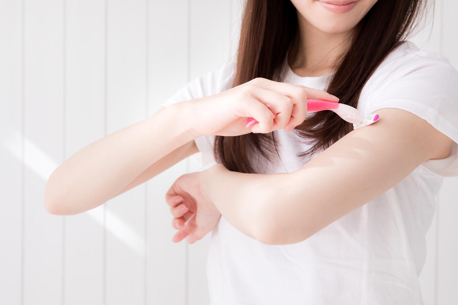 「T字カミソリで肘上を脱毛する女性」の写真[モデル:川子芹菜]