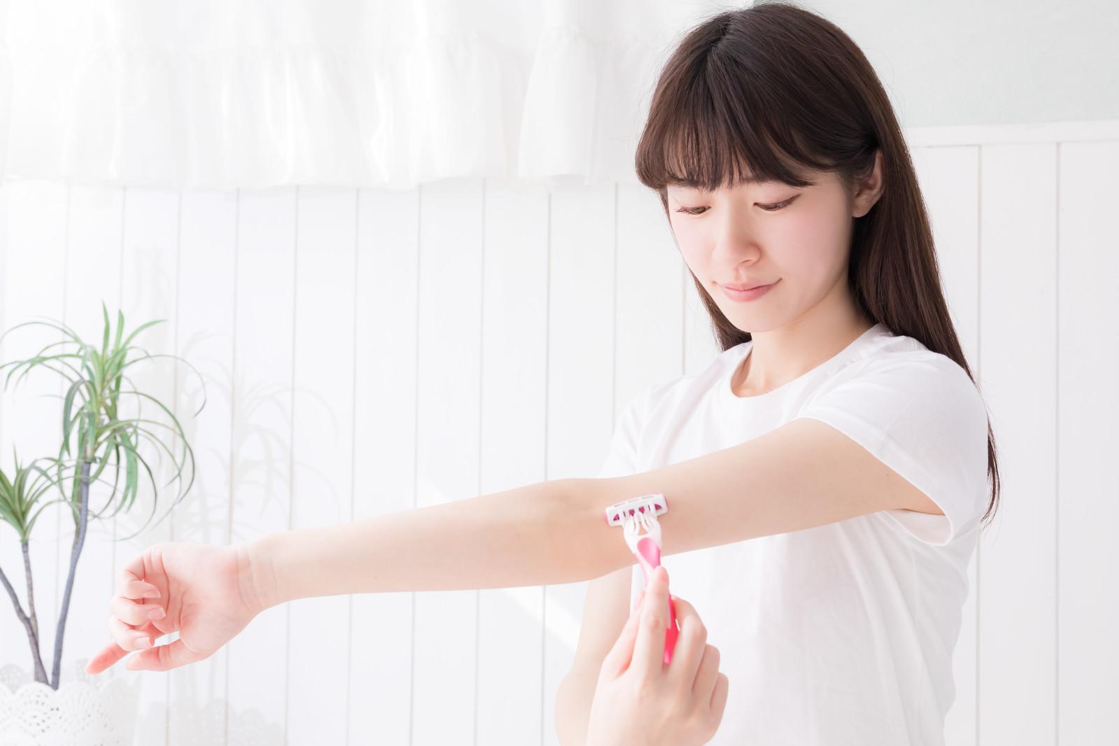 「左腕を伸ばしてT字カミソリで脱毛する女性」の写真[モデル:川子芹菜]