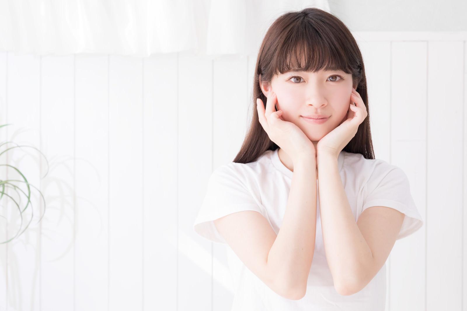 「白い壁の前で顎乗せポーズする女性」の写真[モデル:川子芹菜]