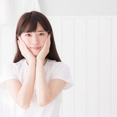両手を顔に添える色白の女性の写真