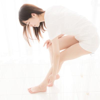 椅子に腰掛け左足の張りを気にする女性の写真