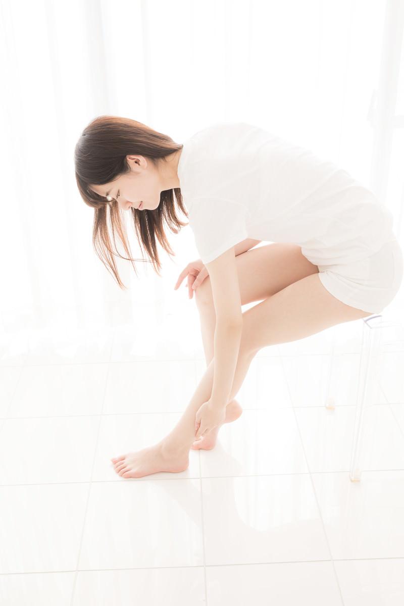 「椅子に腰掛け左足の張りを気にする女性」の写真[モデル:川子芹菜]