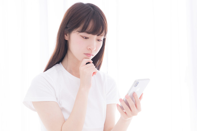 スマホを眺めて考え込む白いTシャツの女性の写真