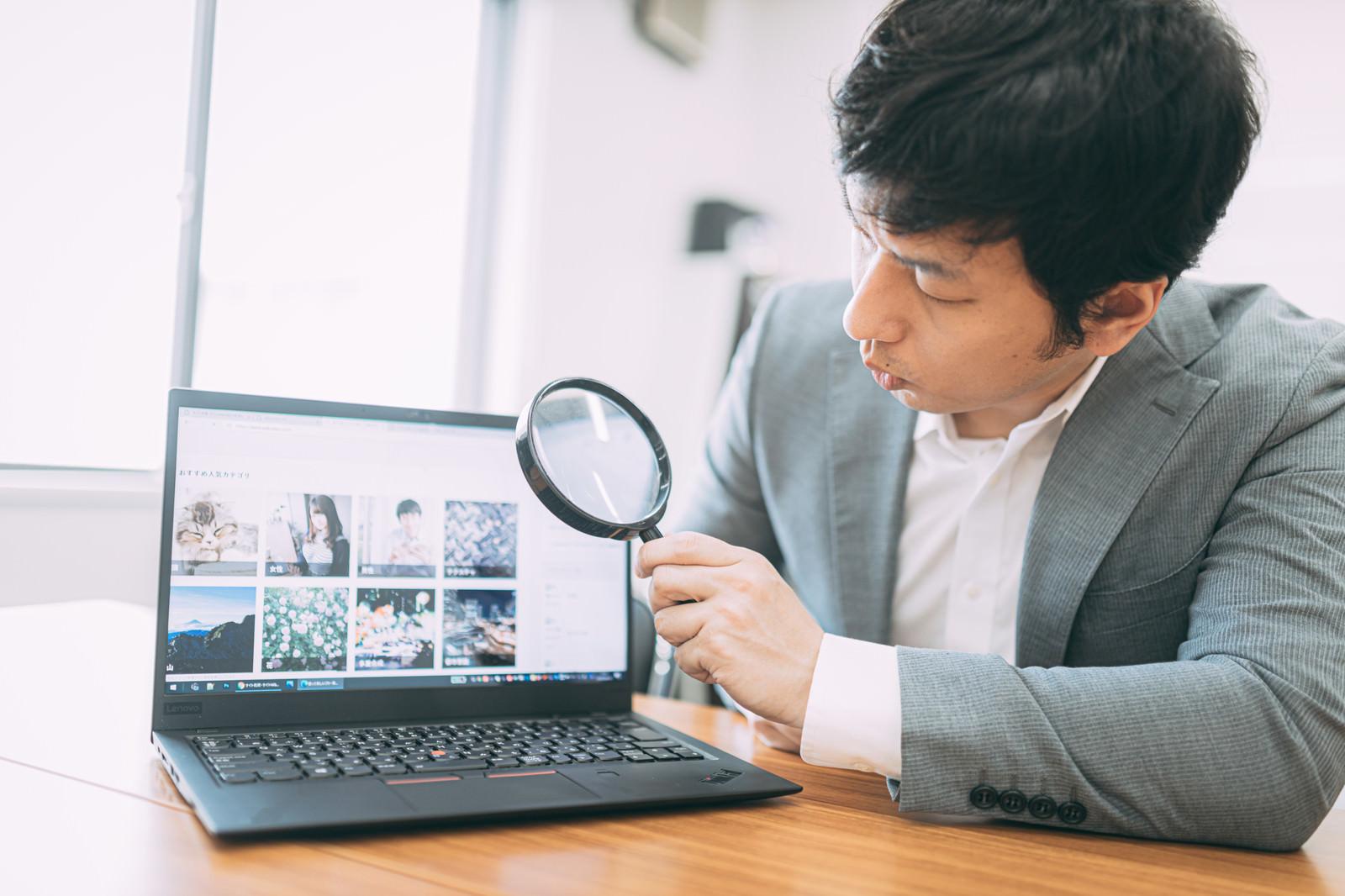 「サイトの価格を鑑定する男性」の写真[モデル:大川竜弥]